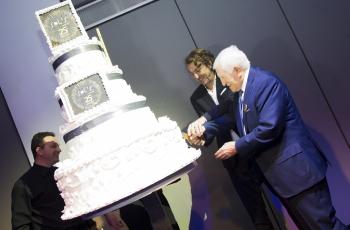 Sol's-Gründer und -CEO Alain Milgrom schneidet bei den Jubiläumsfeierlichkeiten zusammen mit seinem Vater Salomon Milgrom die Geburtstagstorte an.