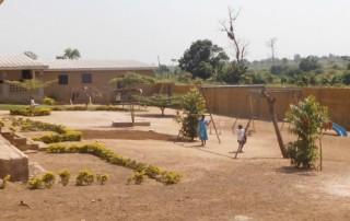 Der neue Hof des Kinderheims mit Spielgeräten und Schutzumfriedung.