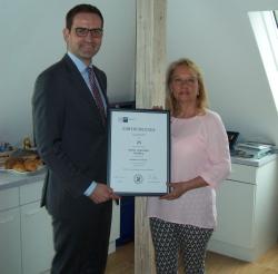 Max-Martin W. Deinhard, stellvertretender Hauptgeschäftsführer der IHK Würzburg-Schweinfurt, übergibt die Ehrenurkunde an Monika Lingenfelder.