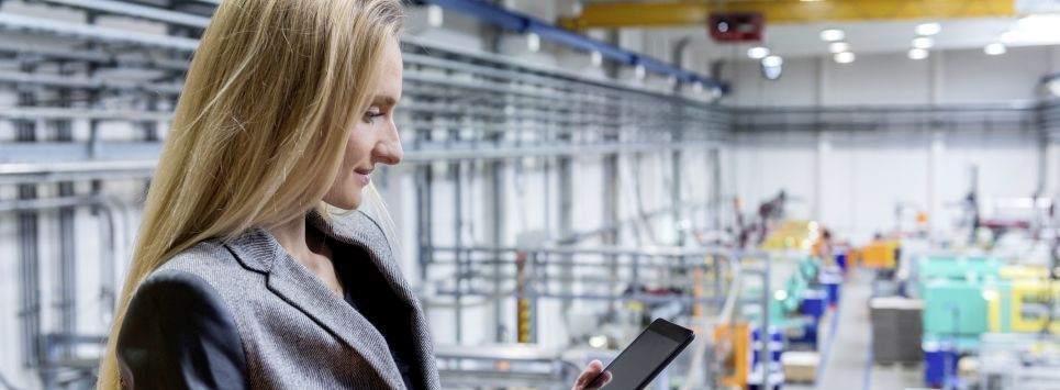 Horizontal color image of blond manager working with digital tablet in large futuristic factory. Blond woman standing on top of a balcony. Focus on businesswoman, futuristic machines in background.