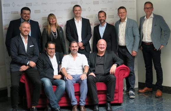 Die Lieferantenpartner der Welcome Home präsentierten sich gemeinsam auf dem roten Sofa. Hintere Reihe (v.l.): Dennis Dennig (Jung Bonbon), Tanja Lumpp (Daiber), Peter Leseberg (Halfar), Dirk Haynberg (aditan), Jan Breuer (mbw), Jochen Ullmann (uma). Vordere Reihe (v.l.): Uwe Thielsch (koziol), Meinhard Mombauer (Reflects by LM Accessoires), Volker Griesel (Fare) und Jürgen Geiger (Geiger-Notes).