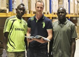 Jamara-Inhaber Manuel Natterer mit den neuen Mitarbeitern Muhammed Jarju (l) und Yusupha Jammeh aus Gambia im Warenlager von Jamara am Stammsitz in Aichstetten.