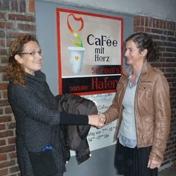 """Anja Mrowka (r), FahnenFleck, übergibt die Kleiderspende an Margot Glunz, Geschäftsführerin des """"CaFée mit Herz""""."""