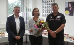 Ritter-Pen-Geschäftsführer Jürgen Riedel (l) und der Betriebsratsvorsitzende Georg Hörr beglückwünschen Christine Ackermann zu 25 Jahren Betriebszugehörigkeit.